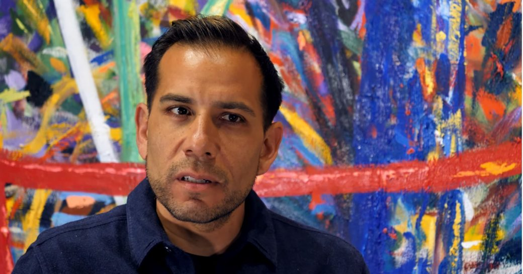Close-up image of a person with dark features, sitting in front of an abstract painting