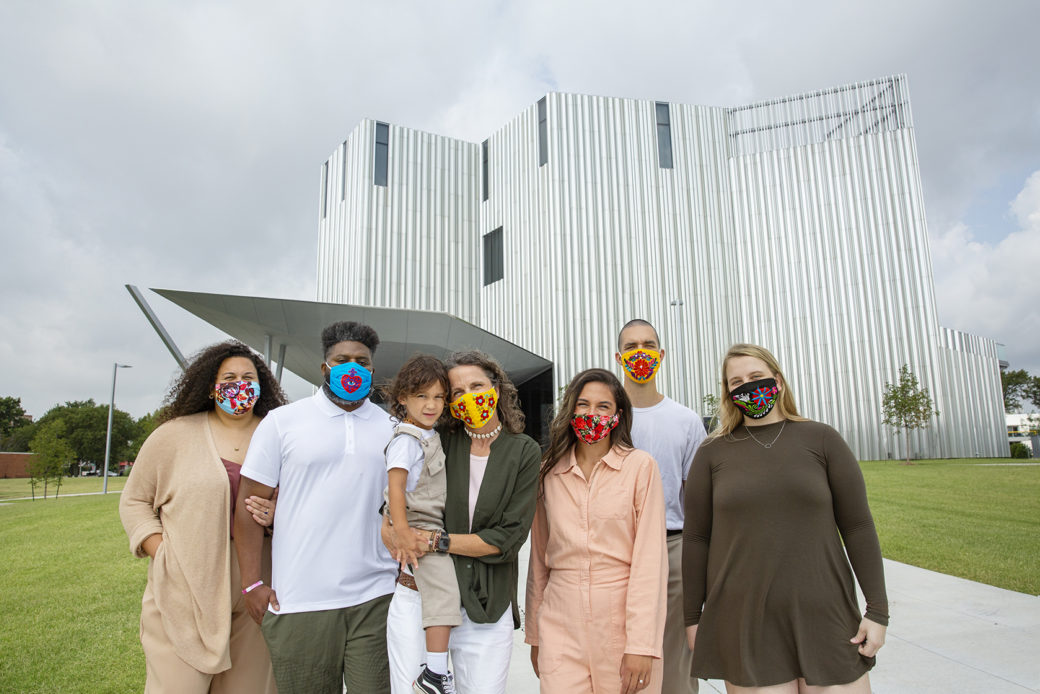 A family in masks stands outside a silver building