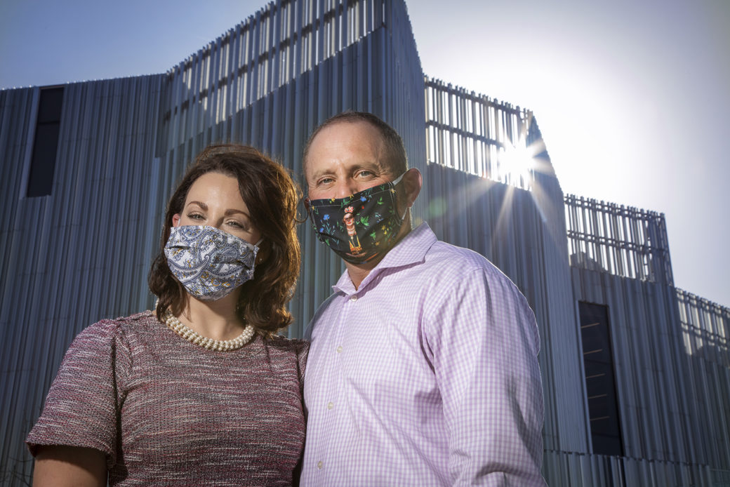 A couple in masks and pastel clothing stand in front of a silver building with the sun peeking through fins at the top