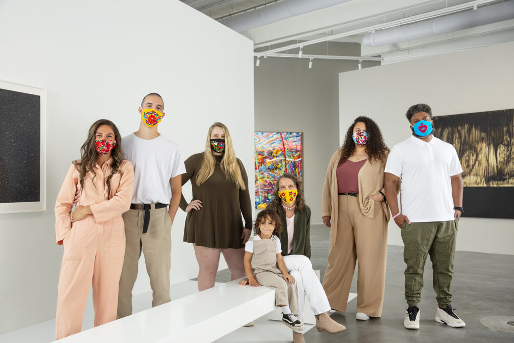 A group of figures wearing face coverings pose for a photo inside an art gallery