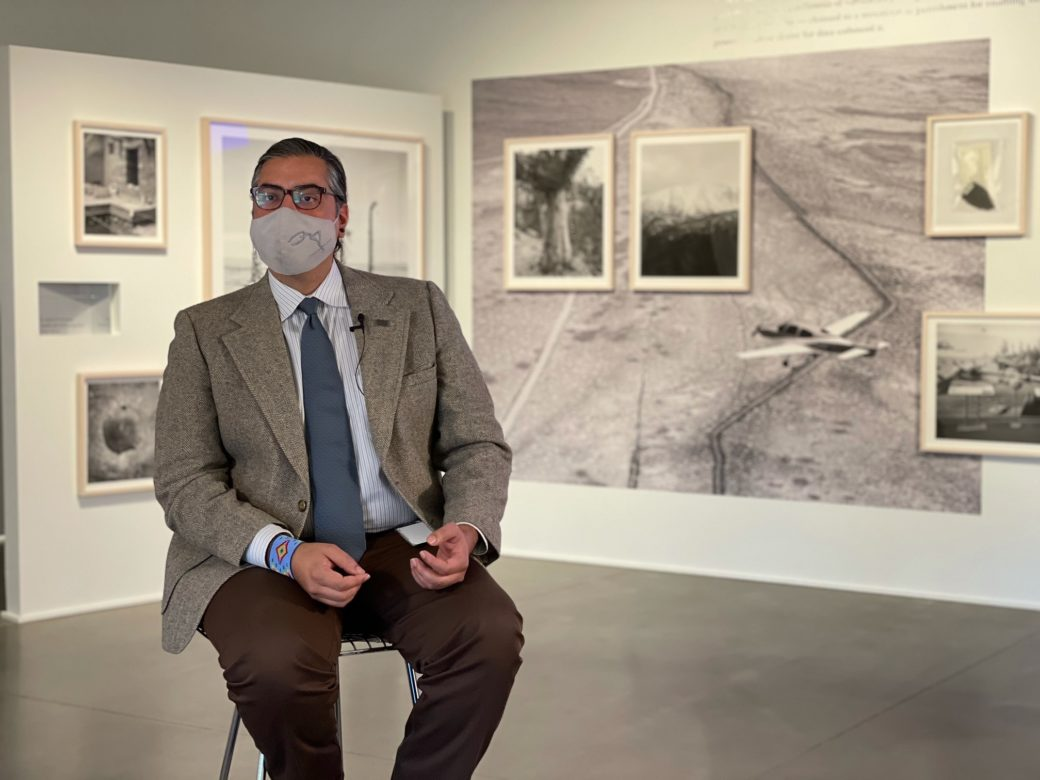 A person with dark features -- wearing a mask, sport coat, tie and cuffed beaded bracelet -- sits in a chair in the middle of an art gallery with photographs on the wall