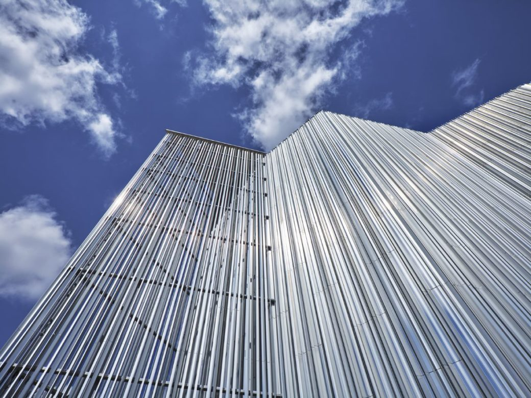 A silver building towers above the camera below a bright blue sky