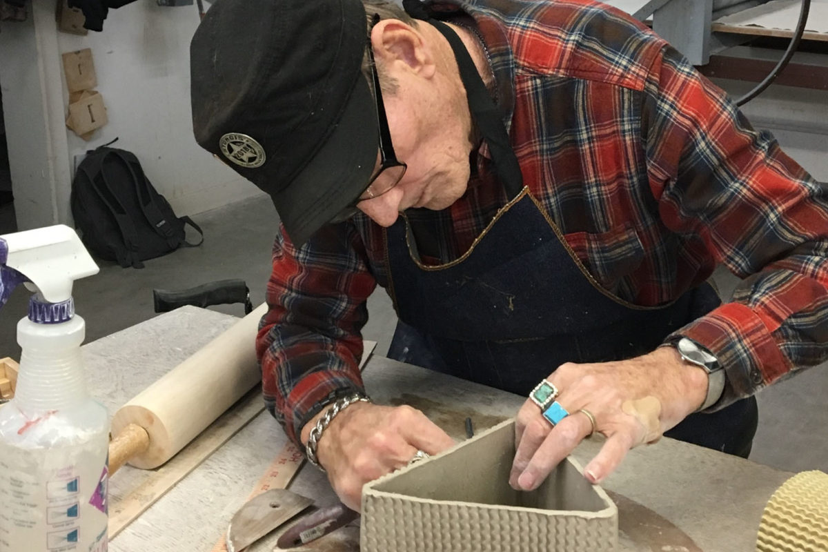 A person in a flannel shirt works on a triangular clay sculpture