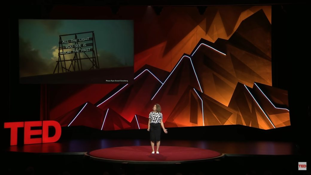 A figure stands on a stage with elaborate background lighting resembling a mountain range, along with a screen featuring an experimental light sculpture