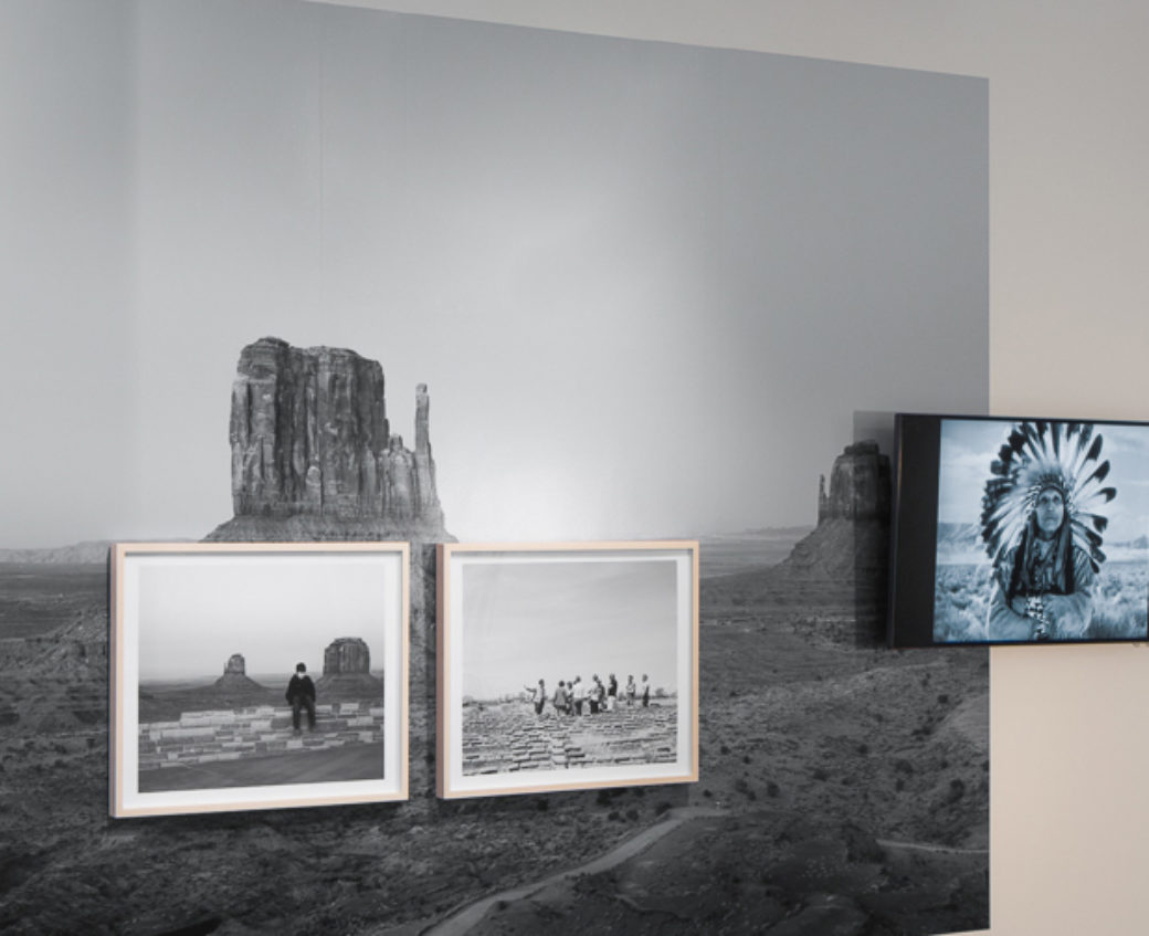 Photographs hang on the wall in an art gallery, depicting southwestern scenes and a person wearing a Native headdress