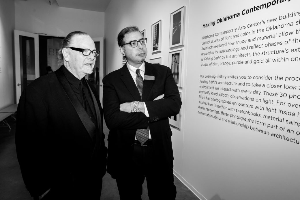 A black and white photo depicts two figures standing before a wall of text describing the origins of Oklahoma Contemporary's new building