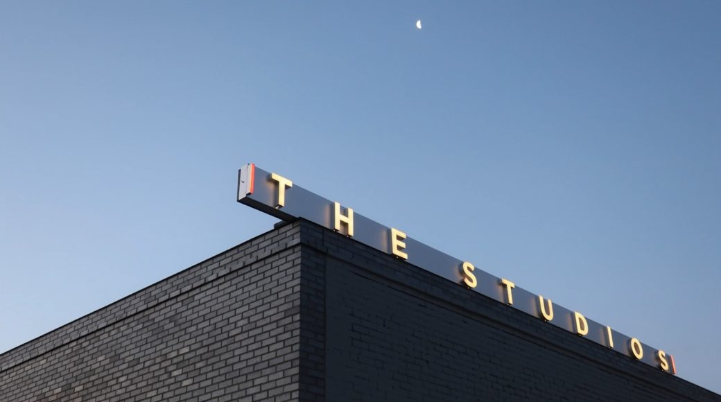 A night scene featuring the corner of a brick building and a sign with the following text: The Studios