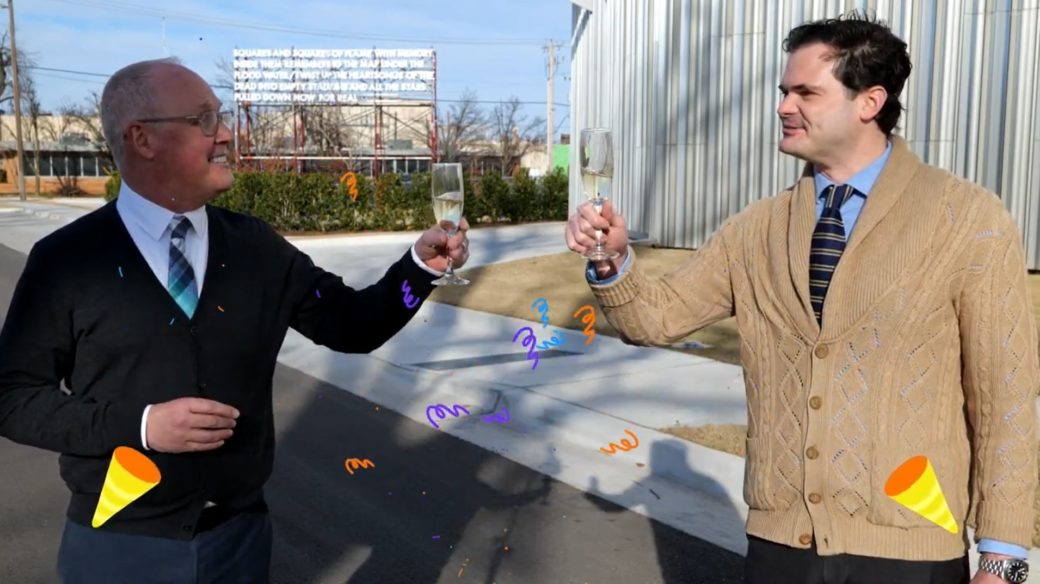 Two people toast champagne glasses outdoors in front of a billboard-style sculpture and metal building