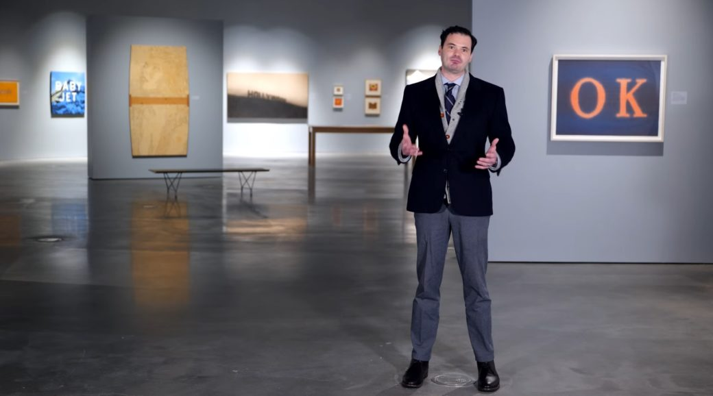 A standing person in business attire gestures with their hands inside an art gallery space