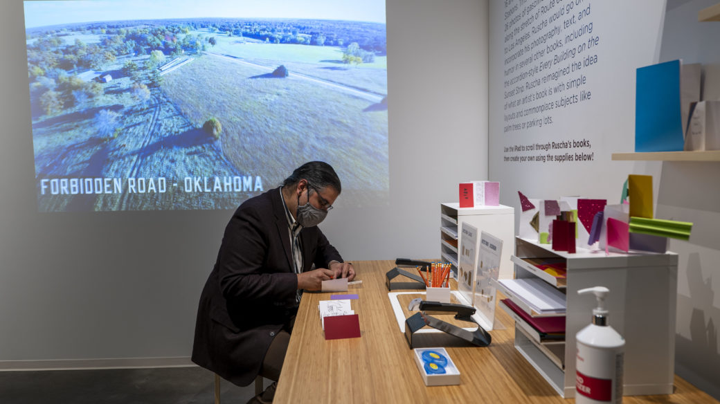 A person wearing a blazer works on a craft project while seated at a table in an educational gallery space