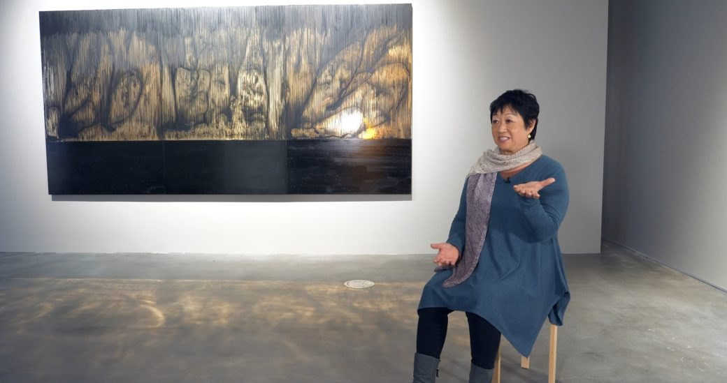 A figure in a blue dress speaks, sitting in front of a reflective work of abstract art