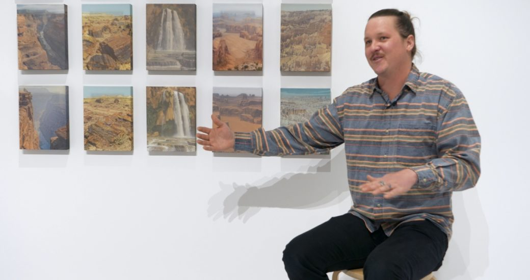 A person seated in front of a panel of 10 pieces of artwork gestures while talking