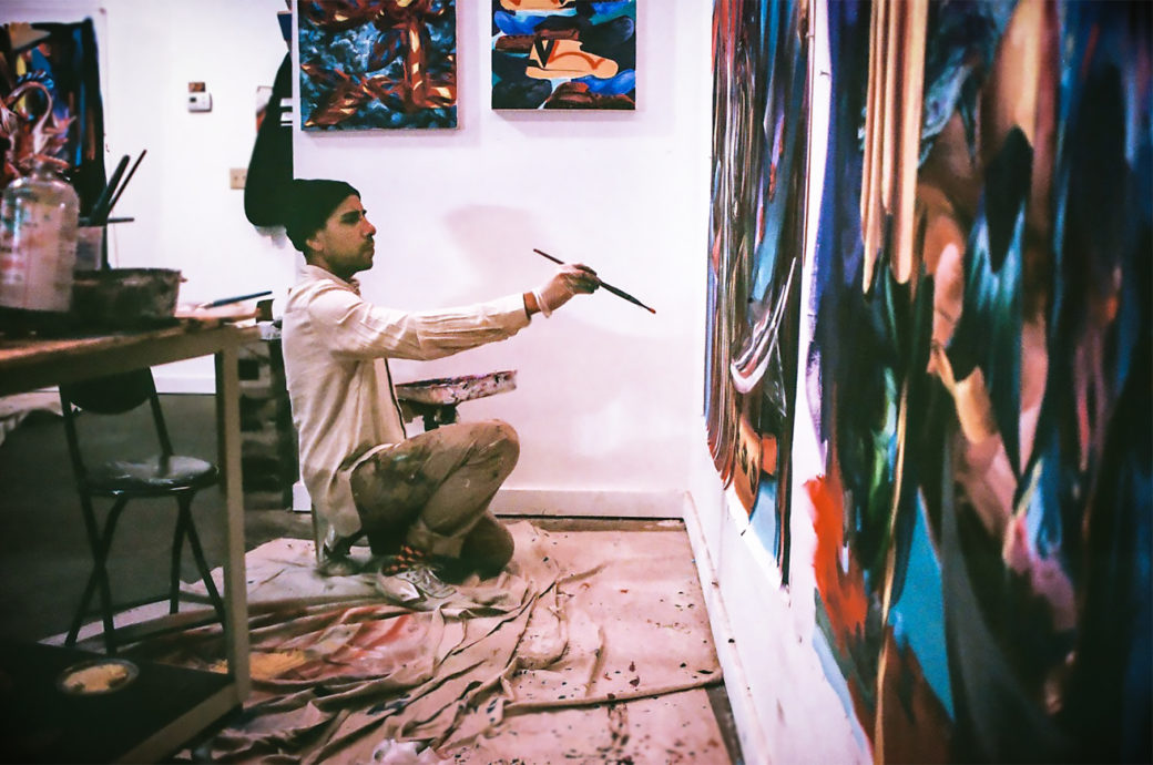 An artist paints a canvas in a studio