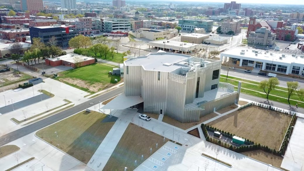 Aerial view of the a silver building with a city skyline in the background