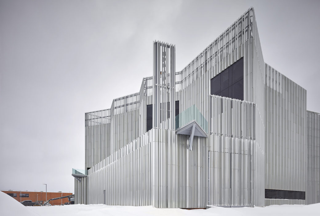 A metal contemporary building with dramatic edges sits in the snow against a gray sky