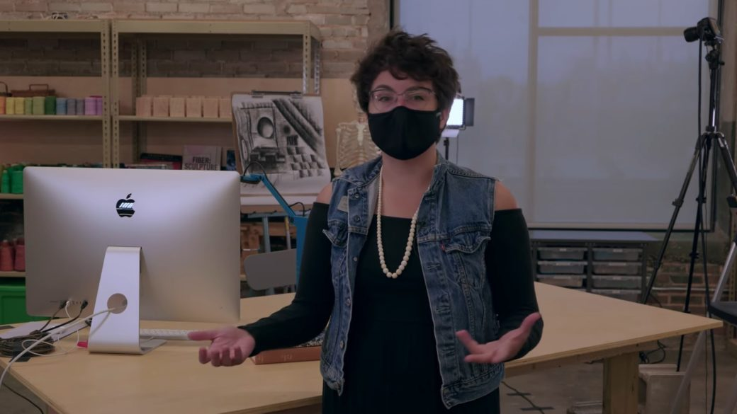 A masked figure gestures in front of a workstation featuring a desktop computer and an in-progress work of art
