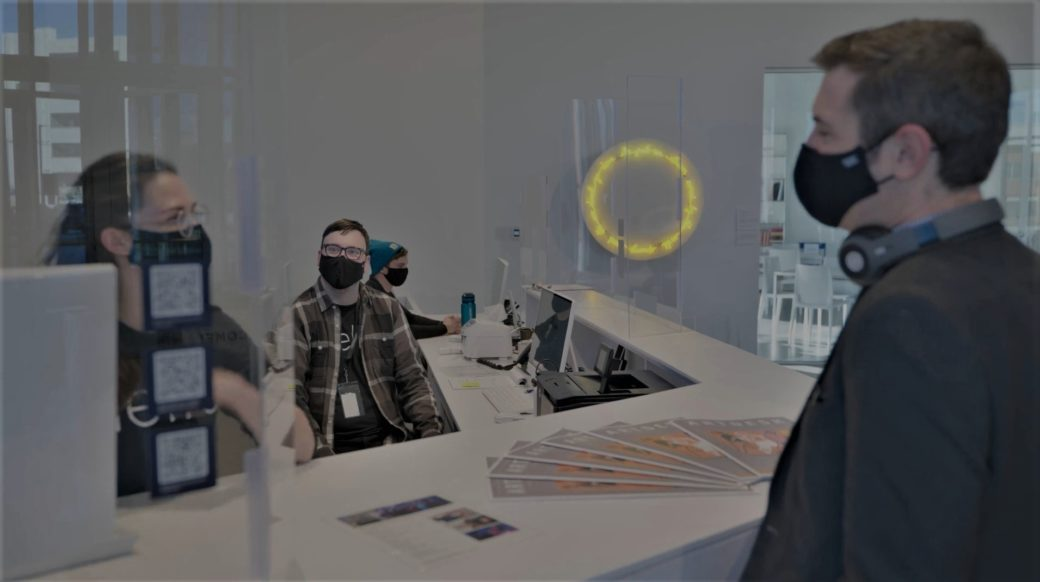A visitor interacts with masked staff members at a large white desk in front of a circular, yellow light sculpture