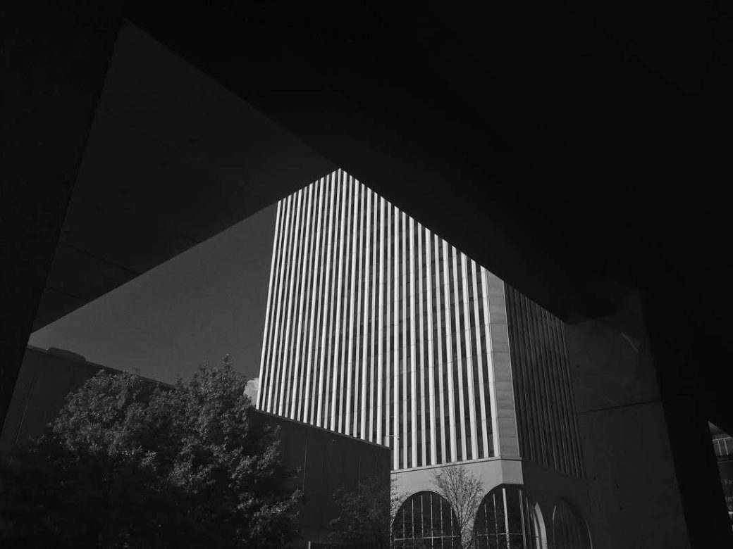 An artistic black-and-white photograph depicts details of a skyscraper building obscured by shadows