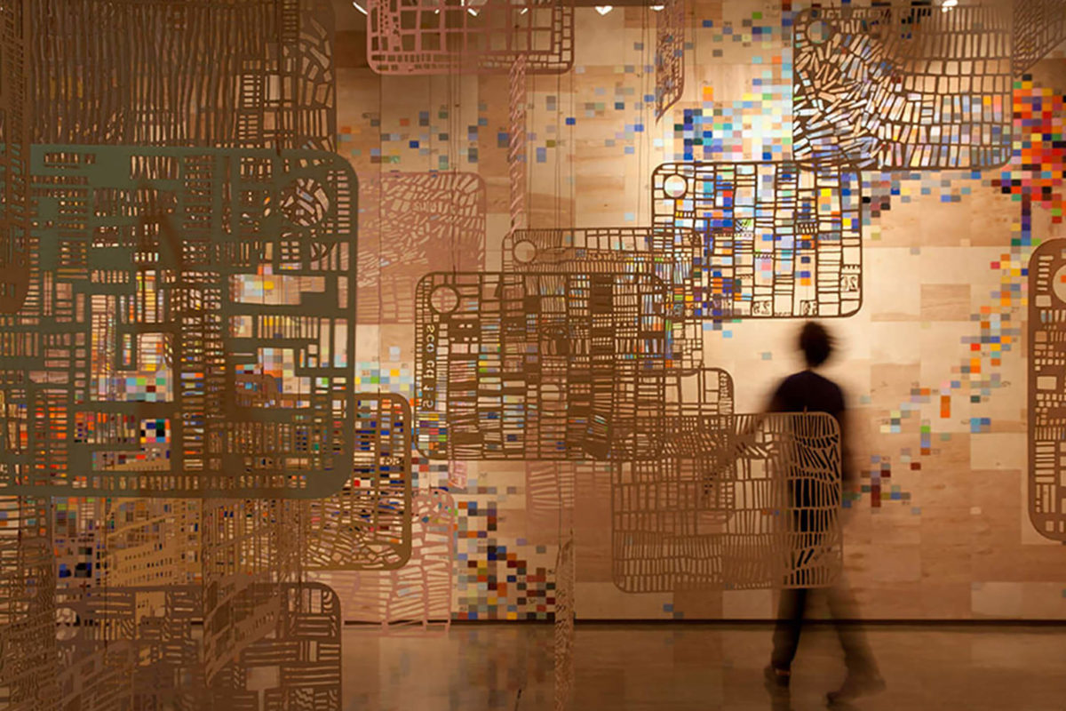 A dark figure walks through a gallery filled with flat, suspended sculptures with cutouts in front of a wall covered in pixelated colors