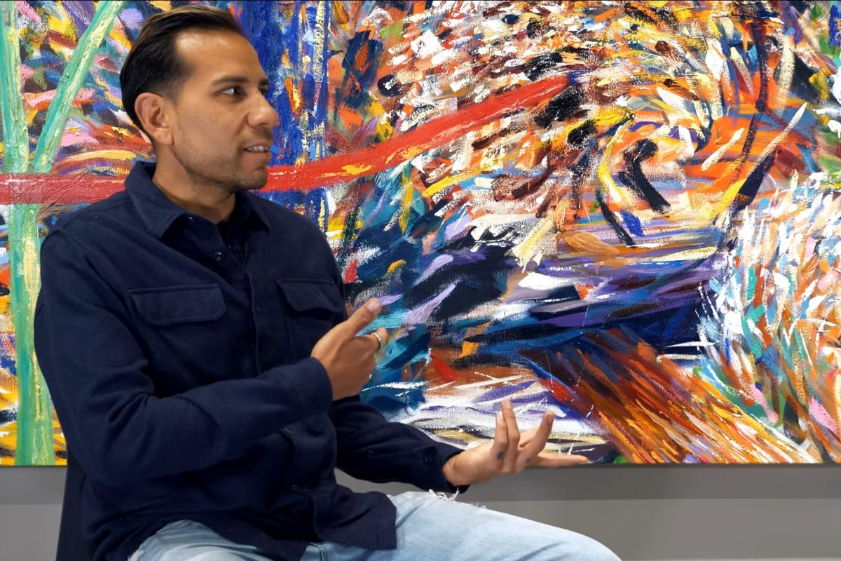 A sitting person gestures in front of a large, colorful, abstract painting