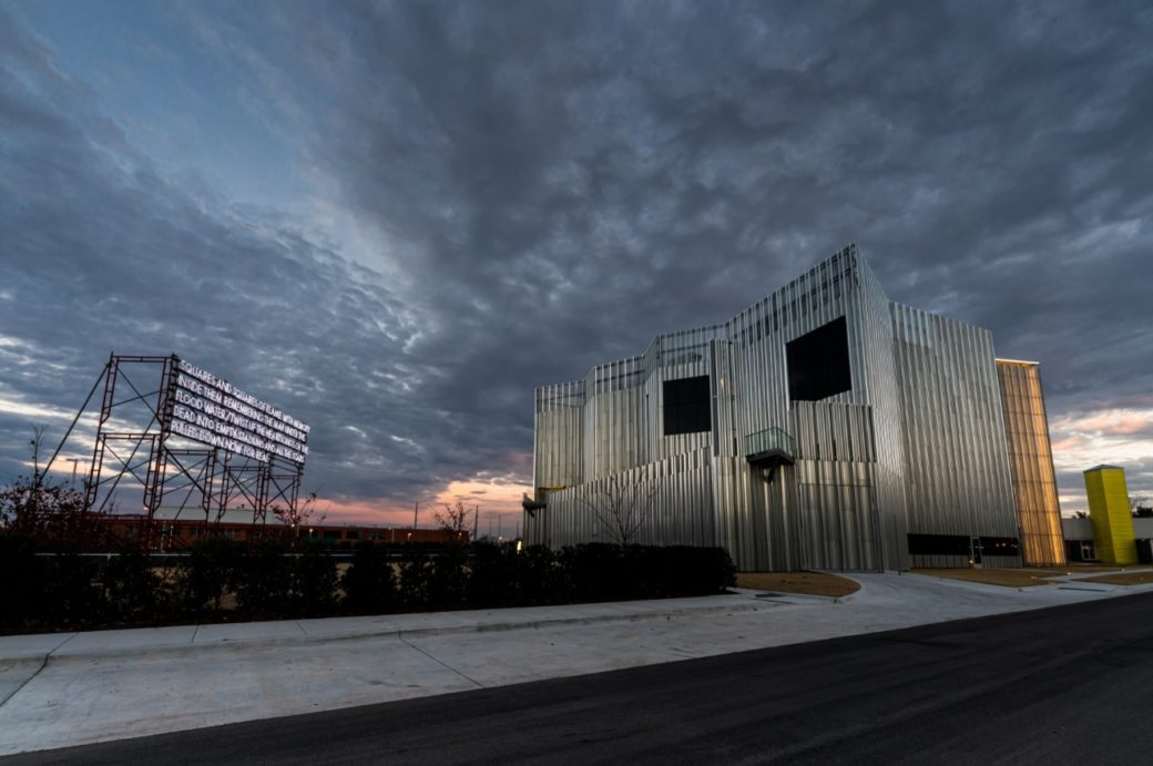 A dramatic sunrise photo of a contemporary metal building next to a billboard-style sculpture with illuminated text