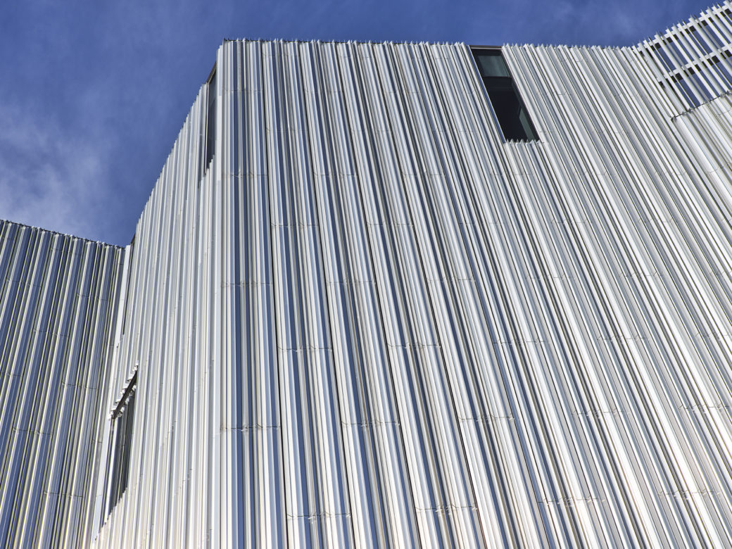 Detail image of the corner of a metallic building set against a blue sky