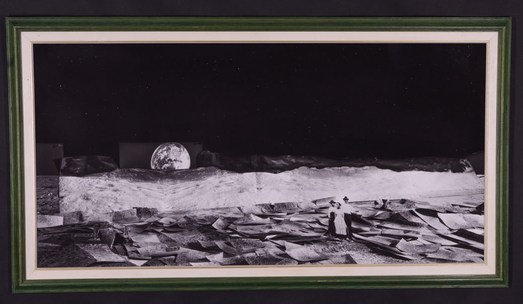 A print of a black-and-white photo collage featuring the earth rising in the background of an abstract landscape with three small figures in the foreground