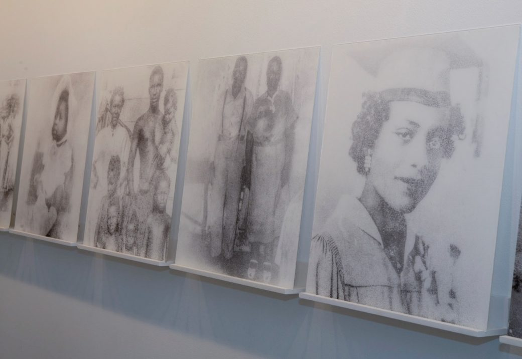 A line of black-and-white photos stand on a white shelf