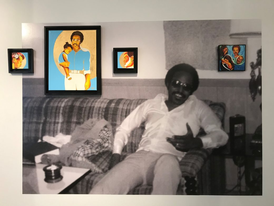 A large black-and-white photo of a man with dark skin sitting on a couch is adhered to a wall, with framed paintings mounted on top of it
