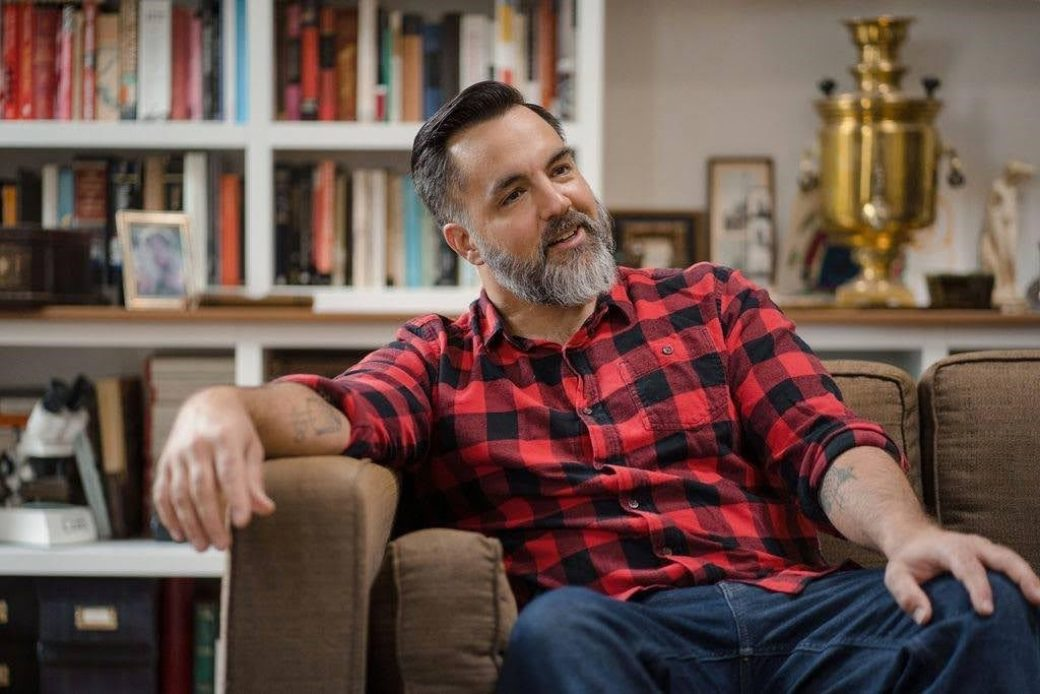 A bearded figure in a red-and-black plaid shirt and jeans sits on a couch in a living room