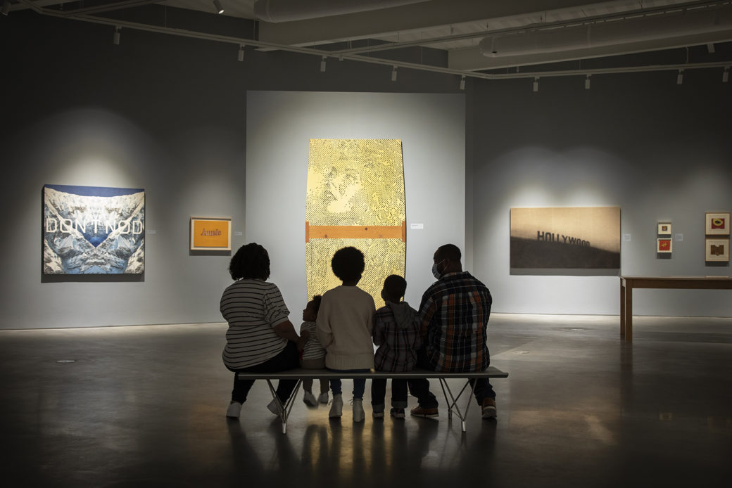 A silhouetted family sits on a bench in an art gallery, looking at works in front of them