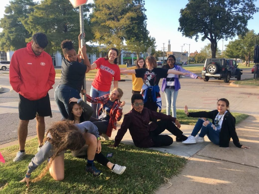 Eleven teenagers pose in various configurations in front of a stop sign