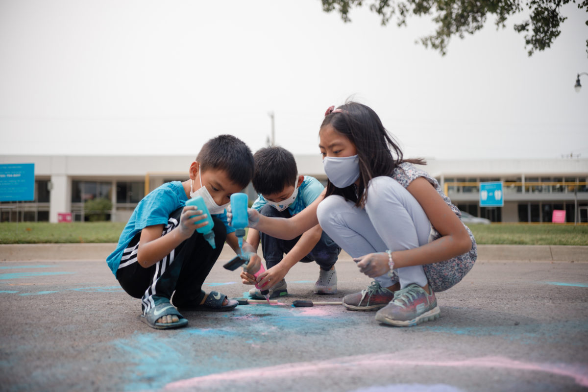 A photo of a group of children in masks drawing with powdered chalk on an asphalt street