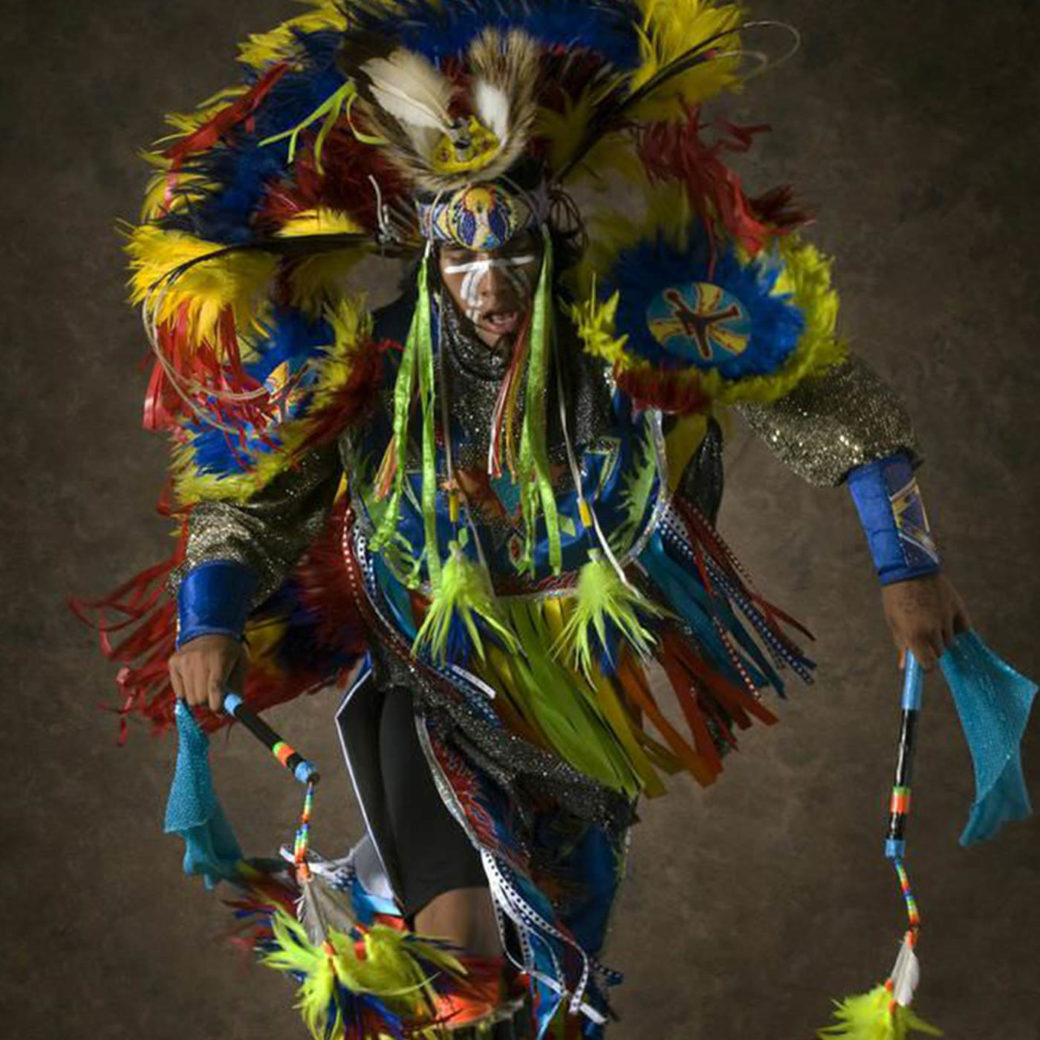 A photo of a ceremonially dressed Native American featuring blue, red, green and yellow highlights
