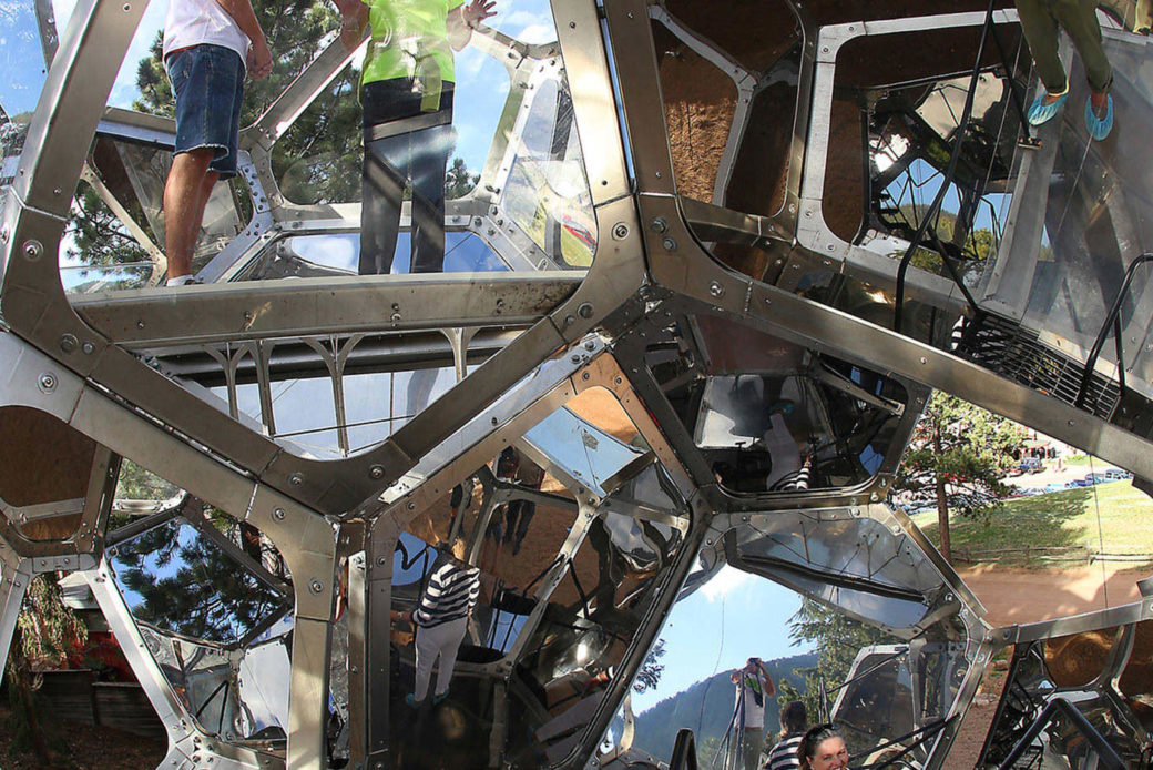 An interior shot of a large metal sculpture -- fractal images of its surfaces and people inside show the different levels of the sculpture