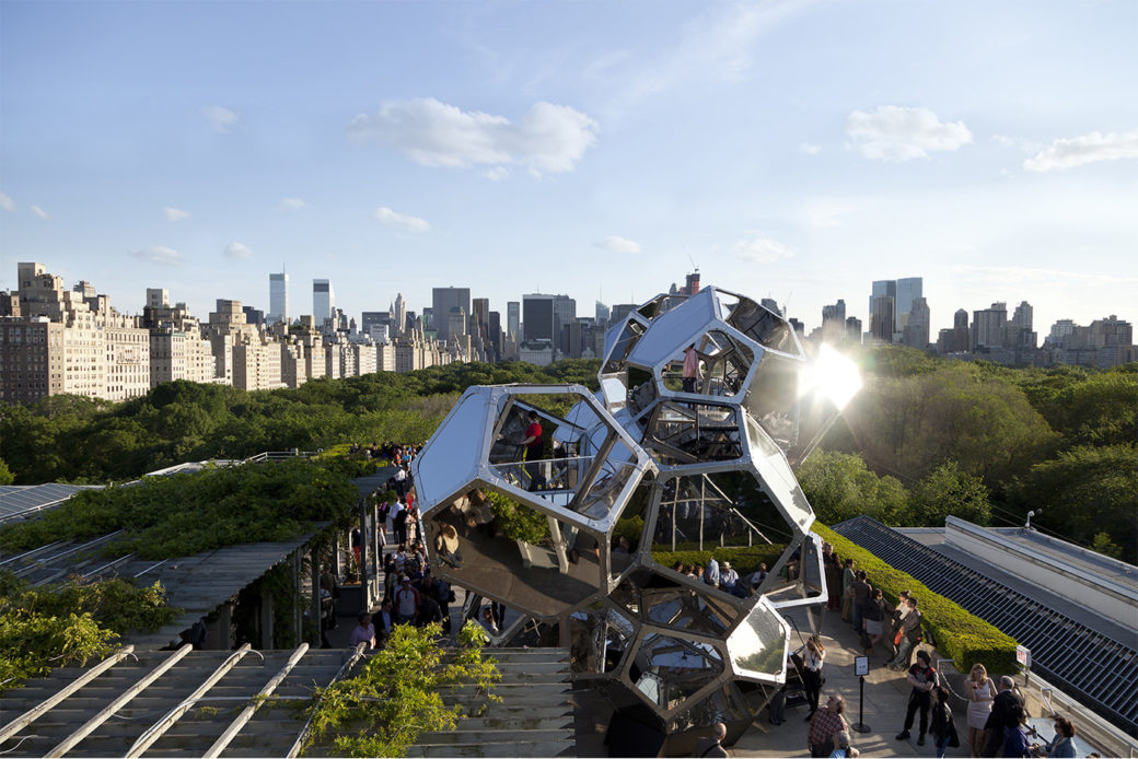 People stand in line outside of a large sculpture that gleams in the sun. In the background are trees and skyscrapers