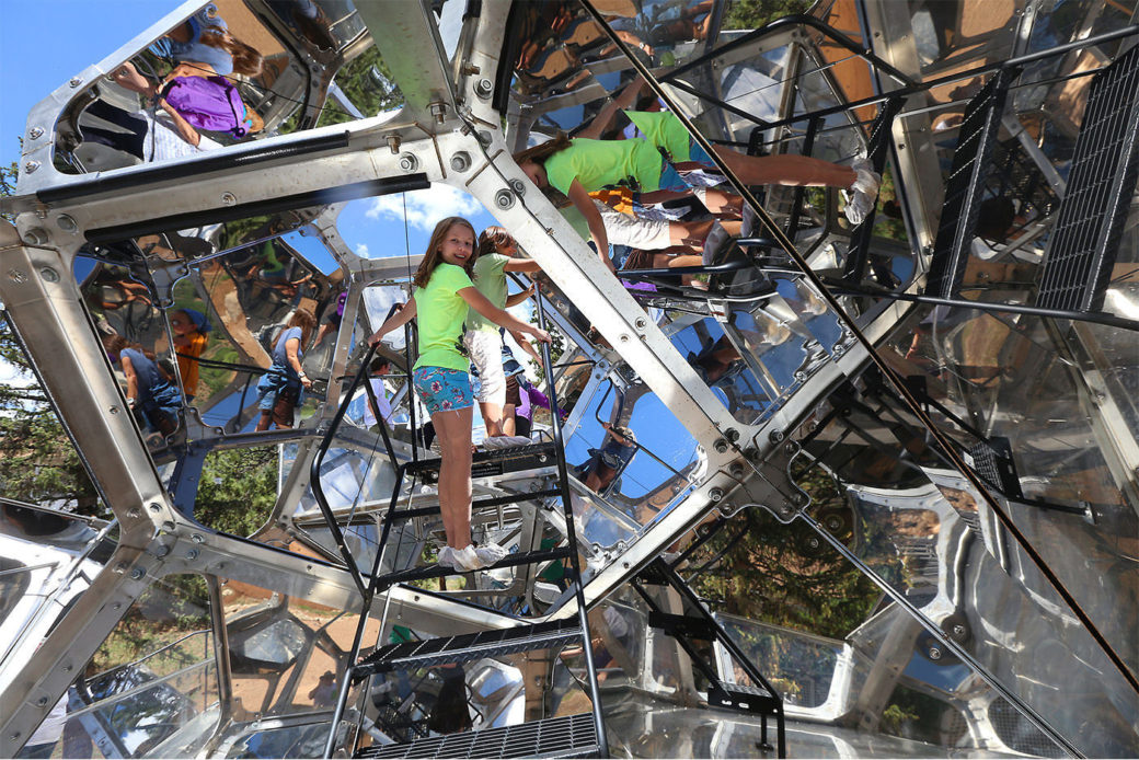 Standing inside a large sculpture, a child on the stairs looks back as their reflection is multiplied and refracted by the shiny interior