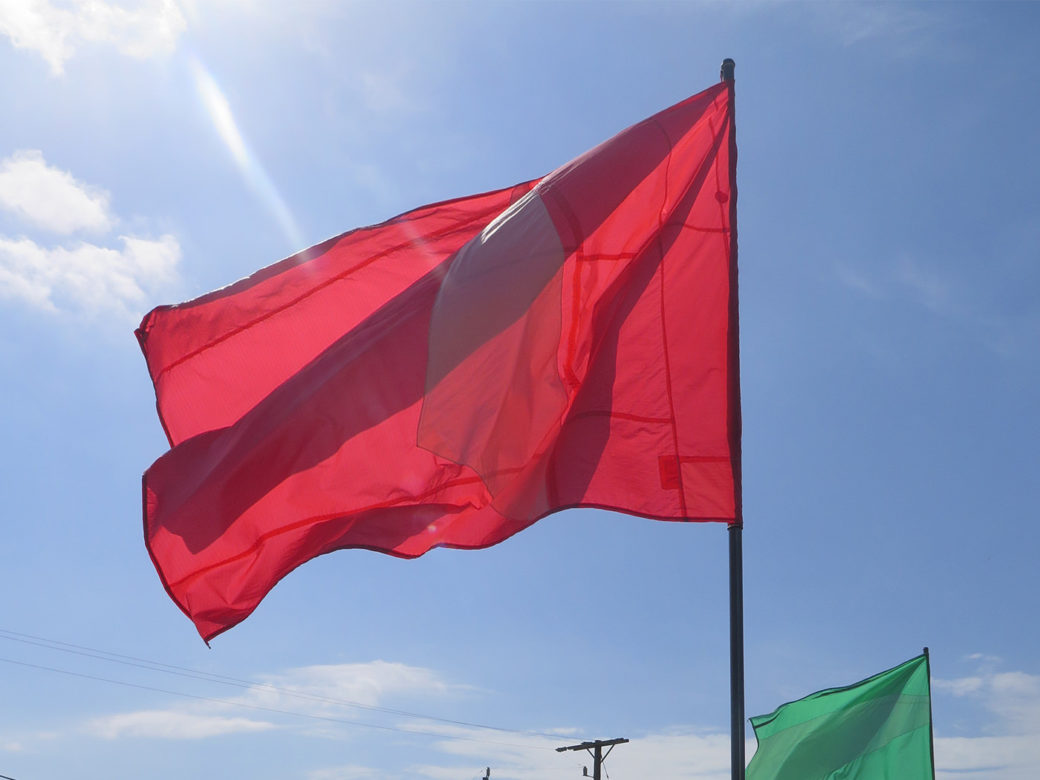 A red flag billows in the wind on a sunny day