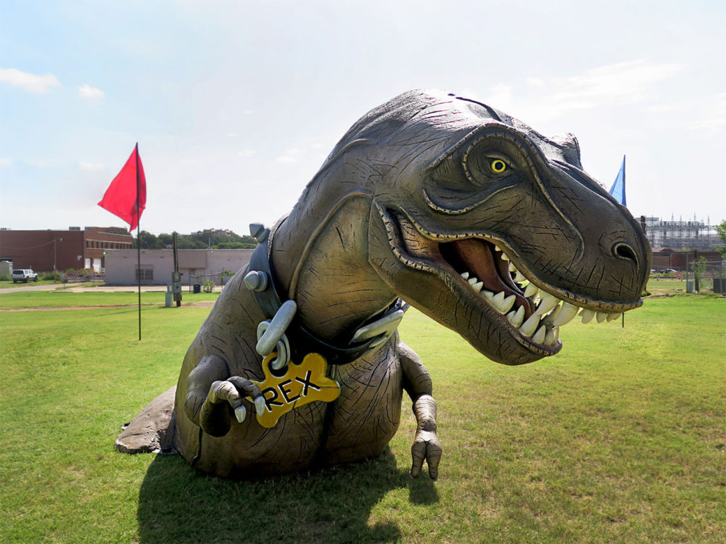 A large dinosaur sculpture with gaping mouth and yellow eyes stands in a park, visible from the waist up, wearing a collar that reads REX