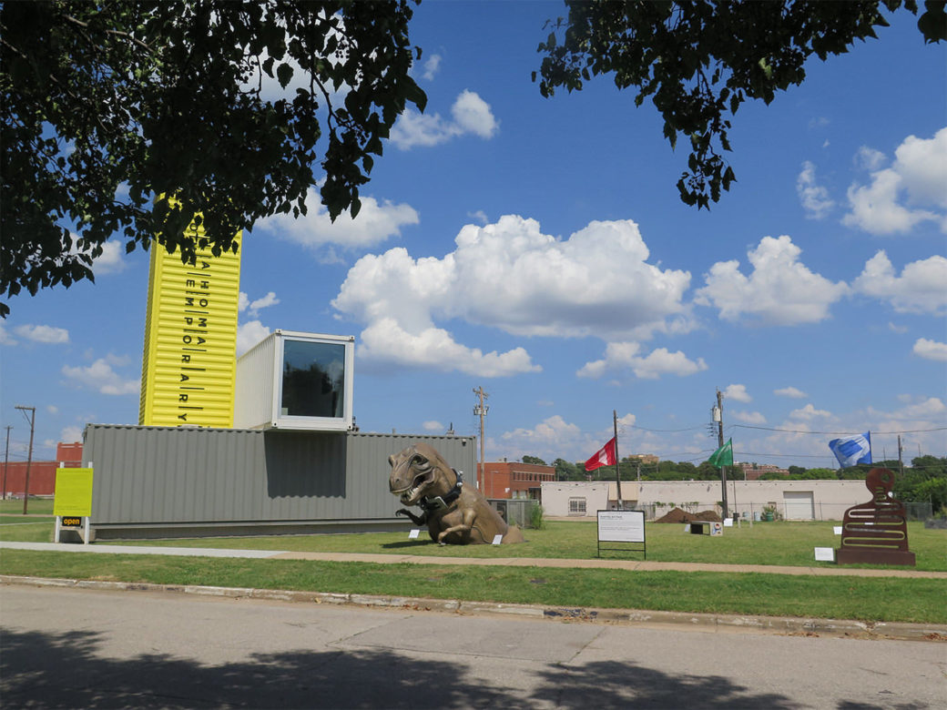 A field features a building of shipping containers and various public artworks, including a large dinosaur and other sculptures
