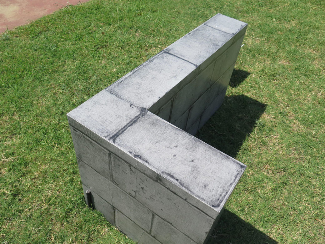 An L-shaped structure wrapped in a gray brick print sits in the grass