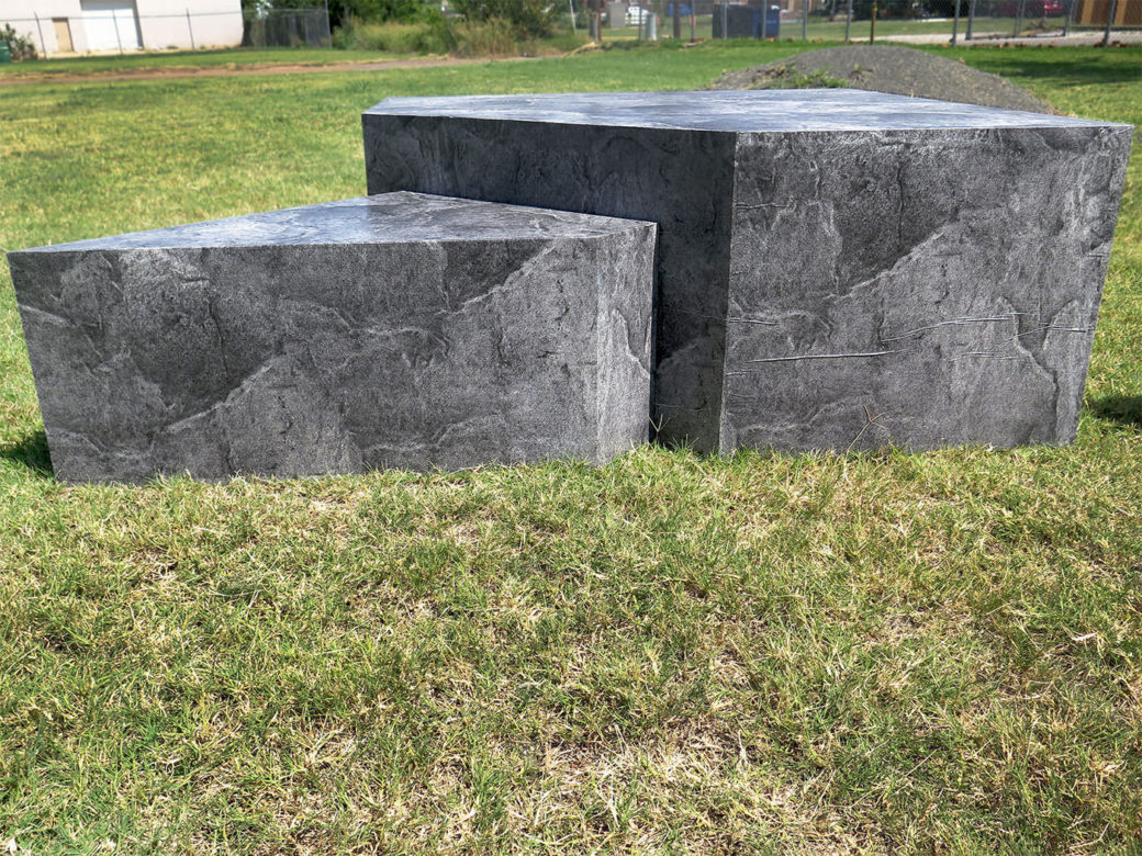 Two platforms wrapped in a gray marble print sit in the grass