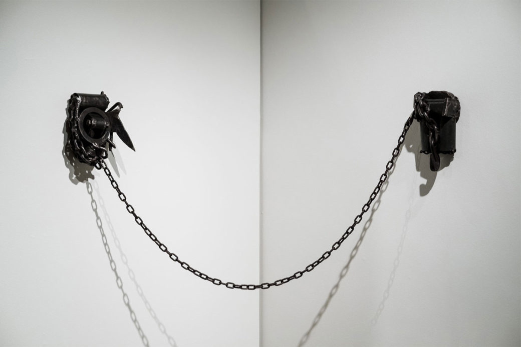 A black metal chain joins two metal sculptures hanging in the corner of two walls