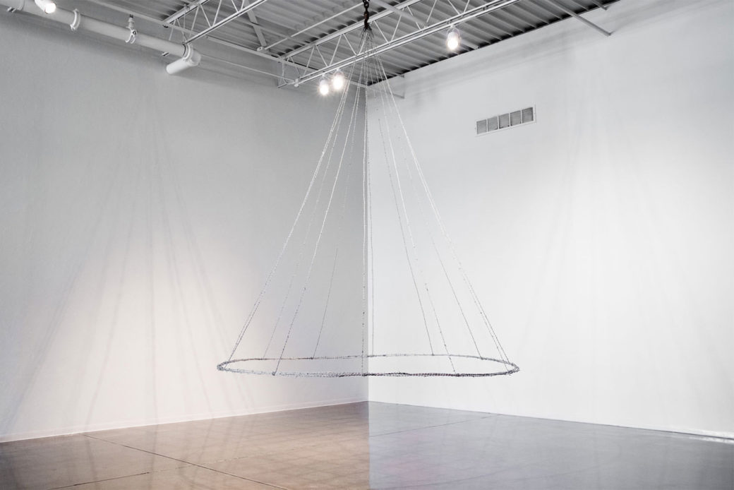 A large sculpture made of wires hangs from the ceiling in a gallery, connected by a hoop at the bottom