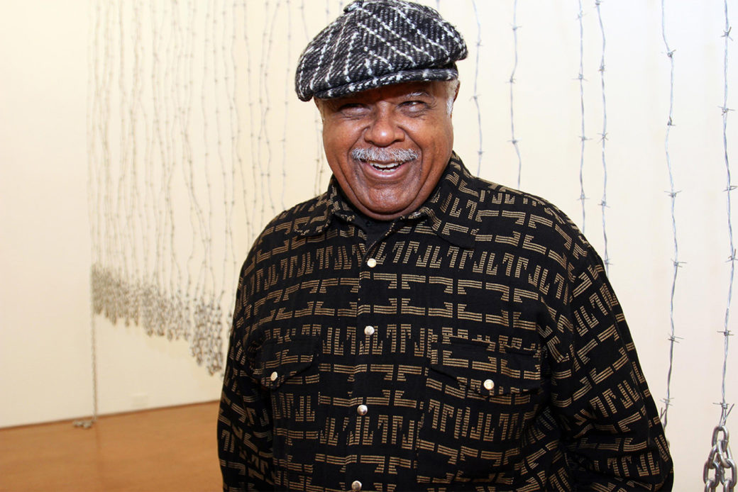 A smiling person in a hat stands in front of a white gallery wall with barbed-wire pieces hanging down