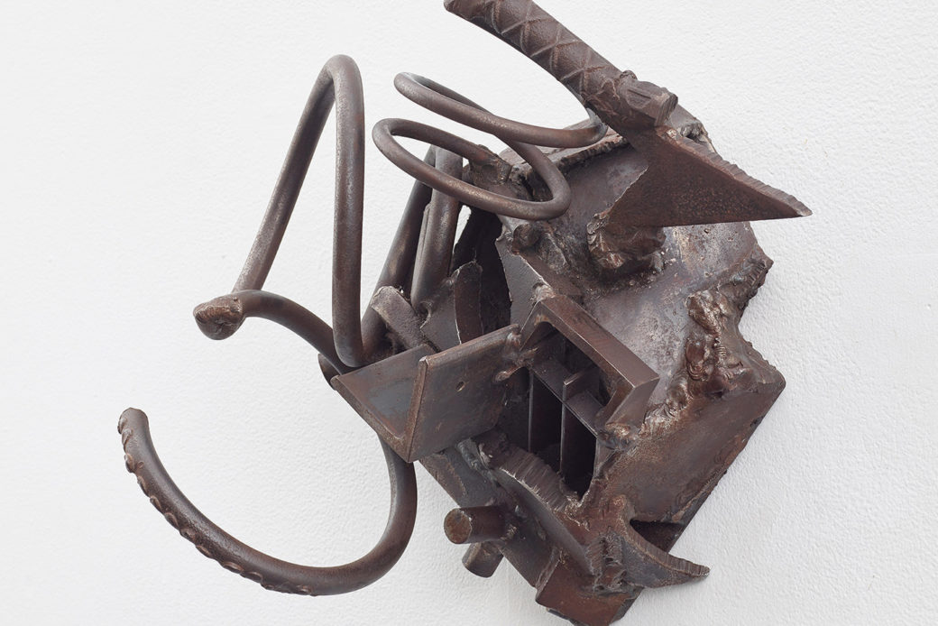 A closeup photo of a sculpture against a white wall, featuring pieces of steel welded together
