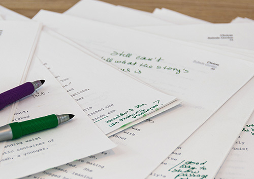 Purple and green pens laying on a pile of papers with typed and handwritten notes.