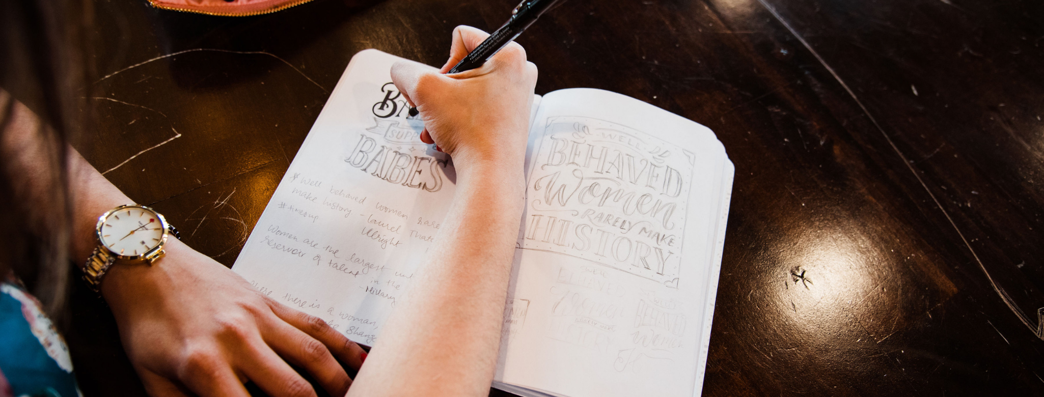 Hand writing with a pen in a notebook on a desk