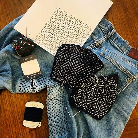 Denim pants with patches, thread, and needle cushion