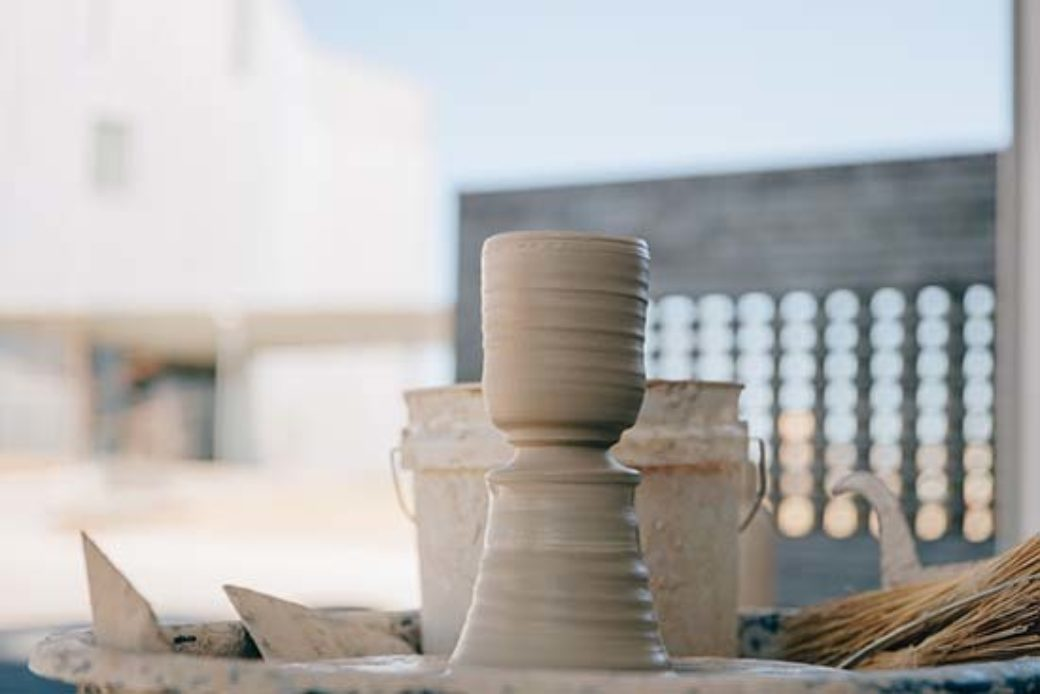 Spacious view of a ceramic goblet taking form on an outdoor throwing wheel